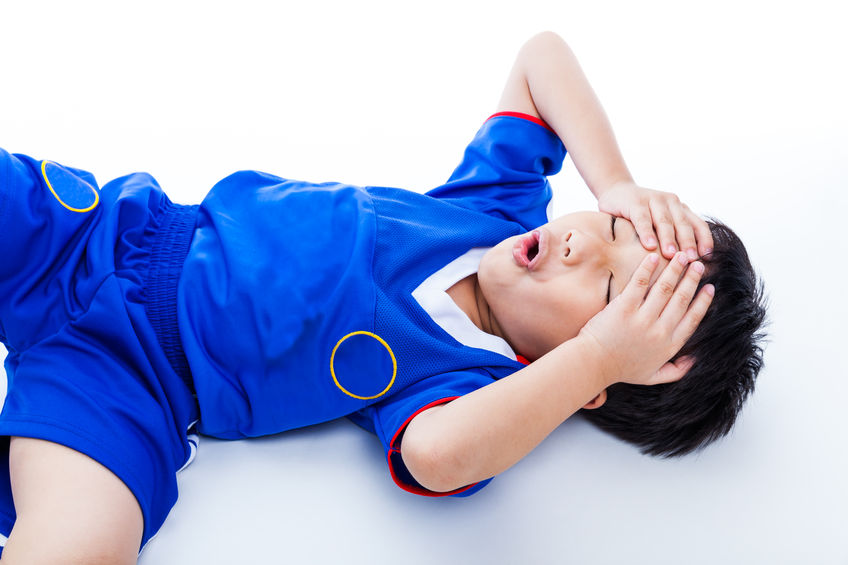 42044674 - sports injury. youth asian (thai) soccer player in blue uniform painful. child closed eyes and touching his forehead. on white background. studio shot. boy lie down. top view
