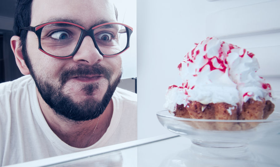 55782354 - funny man sees the sweet cake in the fridge