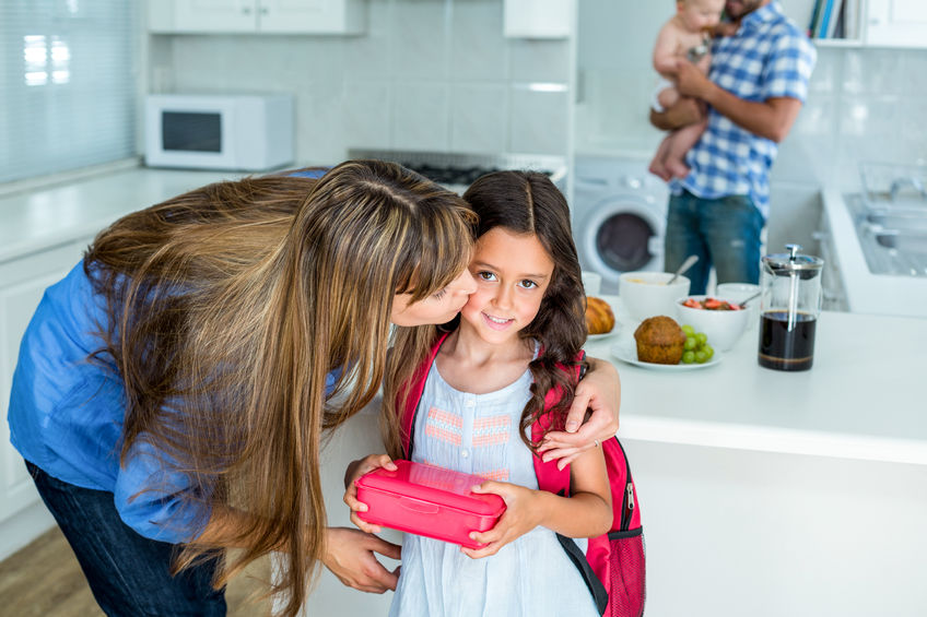 54969452 - mother kissing girl holding school lunch box with family in background at home
